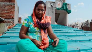 Woman in India sitting on her new roof by ReMaterials.