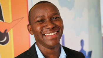 Man smiling in front of colorful background at ShelterTech Kenya event.