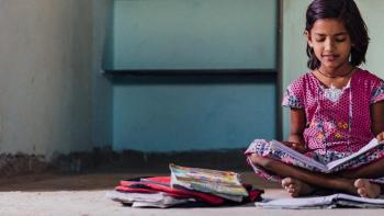 Young girl in India sits reading on her concrete floor.