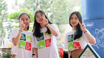 Students from a Habitat school club in Vietnam at a charity sale booth