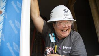 Volunteer smiling on a build site.