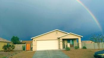 House with rainbow in the background against a dark sky.