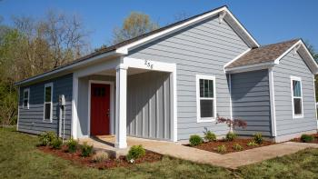 New Habitat house with blue siding and a red door.