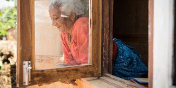 Habitat homeowner looking out of window, Nepal.