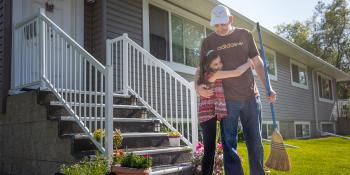 Child hugs father outside their Habitat home
