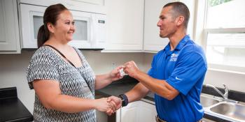 Homeowner receives key from volunteer builder during Home Builders Blitz.