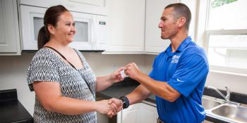 Home Builders Blitz volunteer presents keys to Habitat homeowner