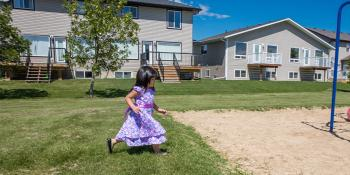 Child plays outside a Habitat house.