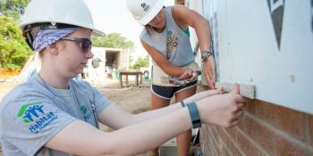 Katy Karl and Julie McNally install siding during the annual Habitat AmeriCorps Build-a-Thon.