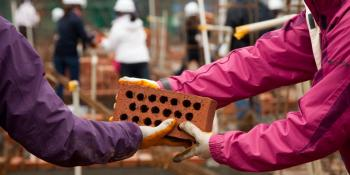 Volunteers pass a brick on a Habitat build site