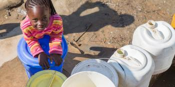 a girl with water tanks in Zambia