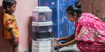 Woman getting water from a Dhaka water filter, Why is clean water important? Habitat for Humanity