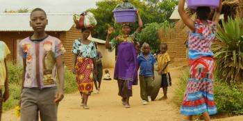 Malawi women using their heads to carry buckets of water.