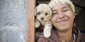 Woman smiles with puppy.