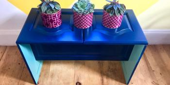 DIY plant stand with three plants.