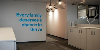 "Empty office with the words ""Every family deserves the chance to thrive"" on the wall."