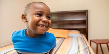Boy smiling as he's sitting on his bed.