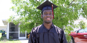 young man in graduation cap and gown smiling in front of his Habitat home.