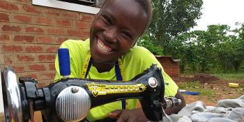 Photo: Evelyn, who took part in the vocational skills training in Uganda, received a Singer sewing machine as part of the start-up tool kit.
