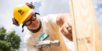A volunteer hammers on a build site.