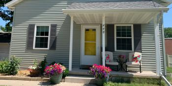 Habitat home in spring with a bright yellow door and pink flowers in front.