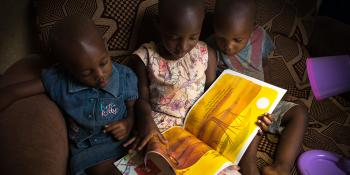 Photo: children reading a book on a sofa at home