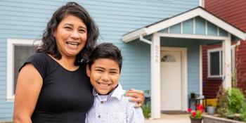 Mother and son smiling in front of their blue house.