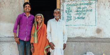 Indian family of three in colorful clothing stand in front of their concrete home.