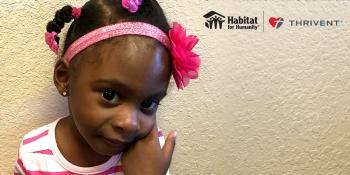 Young girl with pink bow. Habitat and Thrivent Financial logos