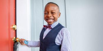 Boy in bow tie smiling and unlocking door.