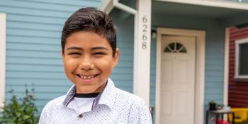 young boy smiling in front of his blue Habitat house.