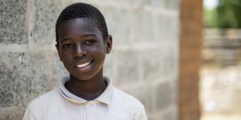young Zambian boy smiling in front of concrete block Habitat home.