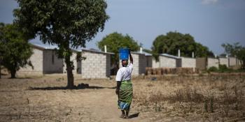 Margaret carries water from the nearby access point to her home in Zambia built by Habitat Zambia, which feature concrete block construction and securely fastened roofs.