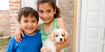 Two children smiling with puppy in front of house