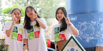 Students from a Habitat school club in Vietnam at a charity booth