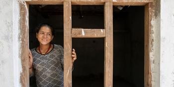 Nepal woman homeowner smiling in the framing of her future Habitat home.