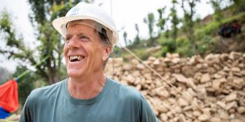 Man in Habitat hard hat smiling on build site.