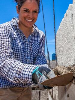 Global Village volunteer working on cement block wall