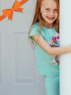Smiling little girl in front of door.