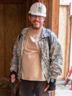 Man in hard hat on build site smiling.