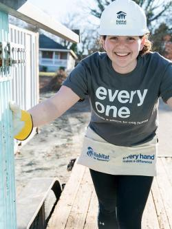 Woman volunteer in hardhat smiling on Habitat build site.