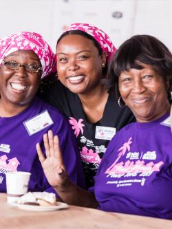 Three women in purple shirts smiling.