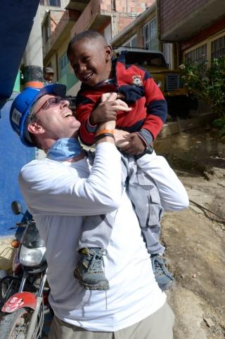 Jonathan Reckford holds a laughing child in Colombia