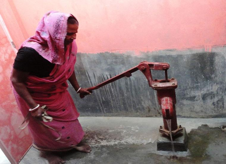 Woman with a water pump, Why is clean water important? Habitat for Humanity