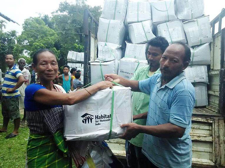 A flood survivor in Assam, India, receiving an emergency kit