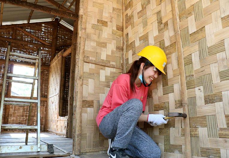 A Japanese volunteer putting up bamboo wall panel at Asia Build, Myanmar.