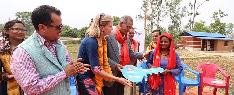 Chameli (far right) receives a symbolic key at the handover of her house