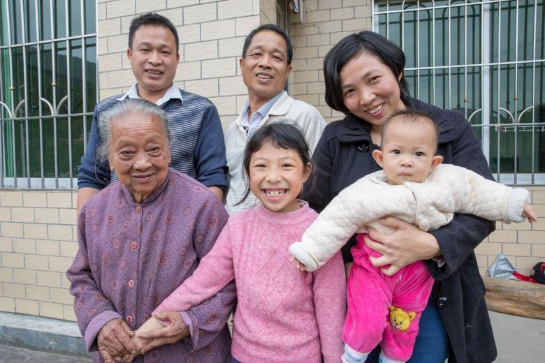 (Clockwise from top left): Zhimin, his father Yongchu, Zhimin's wife Meiling with their youngest daughter Youyou and eldest daughter Xinyi, and his grandmother Nanjiao, in front of their Habitat house in Guangdong, China. Photo: Habitat for Humanity/Jason Asteros.
