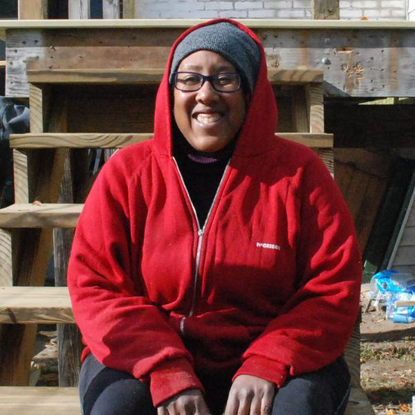 Marguerite in red hoodie sitting on unfinished stairs.