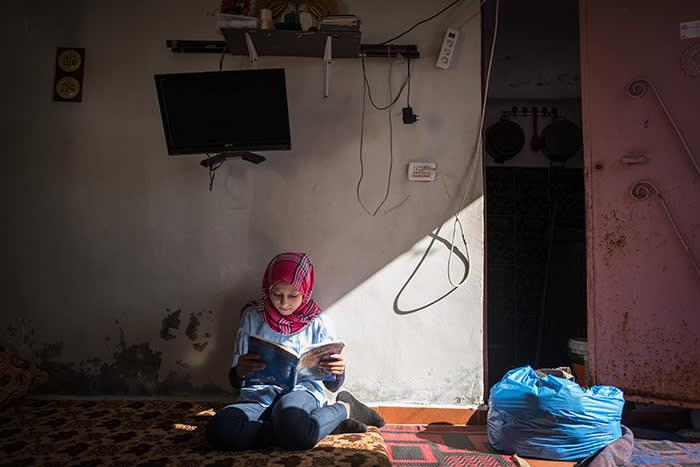 photo by Financial TImes: Lara al-Khaled reading a book sitting on the floor